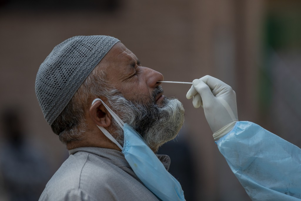A Kashmiri health worker takes a nasal swab sample to test for COVID-19 in Srinagar, Indian-controlled Kashmir, Tuesday, Oct. 6, 2020. India is the se...