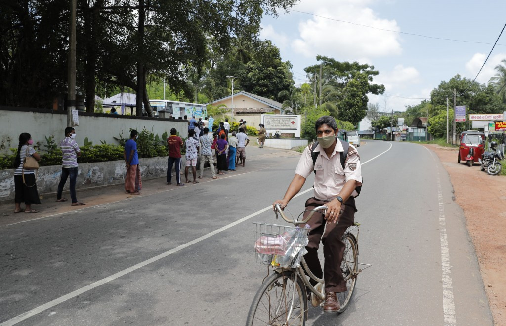 A Sri Lankan man rides a bicycle amid curfew as others wait to give swab samples to test for COVID-19 outside a hospital in Minuwangoda, Sri Lanka, Tu...