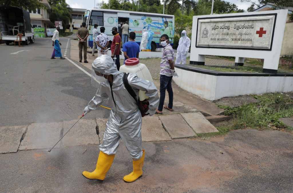 A Sri Lankan health worker sprays disinfectants as people wait to give swab samples to test for COVID-19 near a mobile testing vehicle outside a hospi...