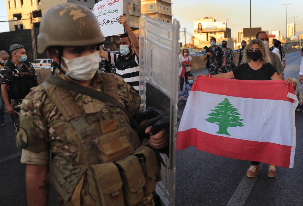 A Lebanese army soldier passes in front of an anti-government protester holding a national flag and blocking a main highway that links Beirut with nor...