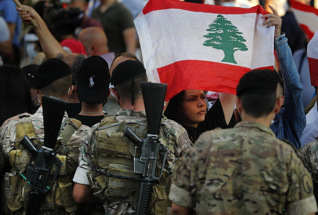 An anti-government protester holds a national flag, as she passes in front of Lebanese army soldiers during a protest against rising prices and worsen...