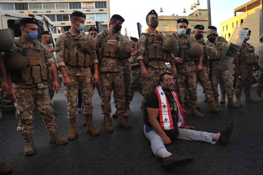 Lebanese army soldiers stand behind a handicapped anti-government protester, sitting on the ground blocking a main highway that links Beirut with nort...