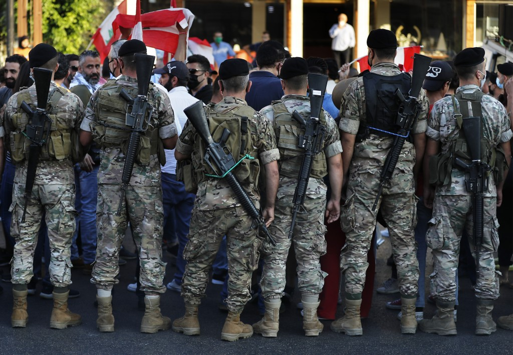 Lebanese army soldier stand in front of anti-government protesters, as they try to get them to unblock a main highway that links Beirut with north Leb...