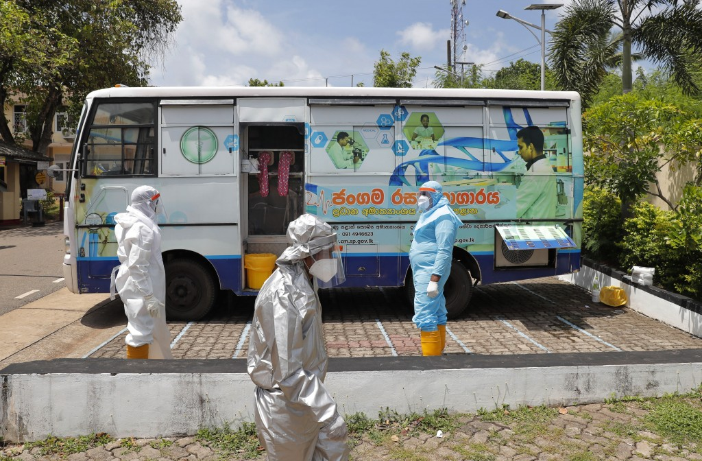 Sri Lankans health workers prepare to take swab samples of people to test for COVID-19 near a mobile testing vehicle outside a hospital in Minuwangoda...