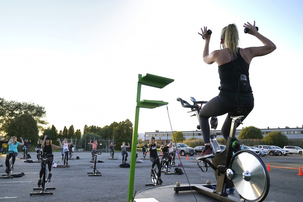 Cycle spinning instructor Alli Sherman, of Newburyport, Mass., top right, leads a spinning class in a parking lot outside Fuel Training Studio, Monday...