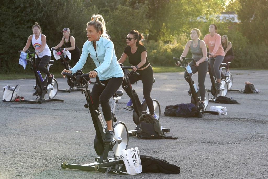 Jackie Brennan, of Merrimac, Mass., front, pedals on a stationary exercise bike with others during a spinning class in a parking lot outside Fuel Trai...