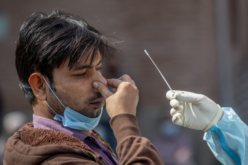 A Kashmiri man reacts as a health worker takes a nasal swab sample to test for COVID-19 in Srinagar, Indian-controlled Kashmir, Tuesday, Oct. 6, 2020....