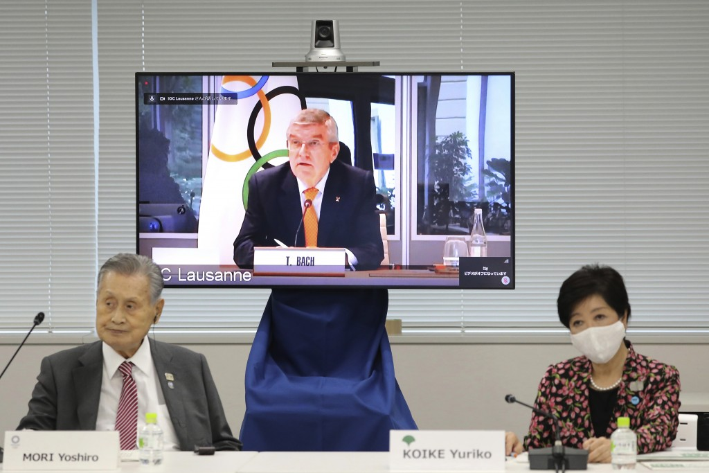 In this Sept. 24, 2020, file photo, IOC President Thomas Bach, on the screen, speaks remotely with Tokyo 2020 Organizing Committee President Yoshiro M...