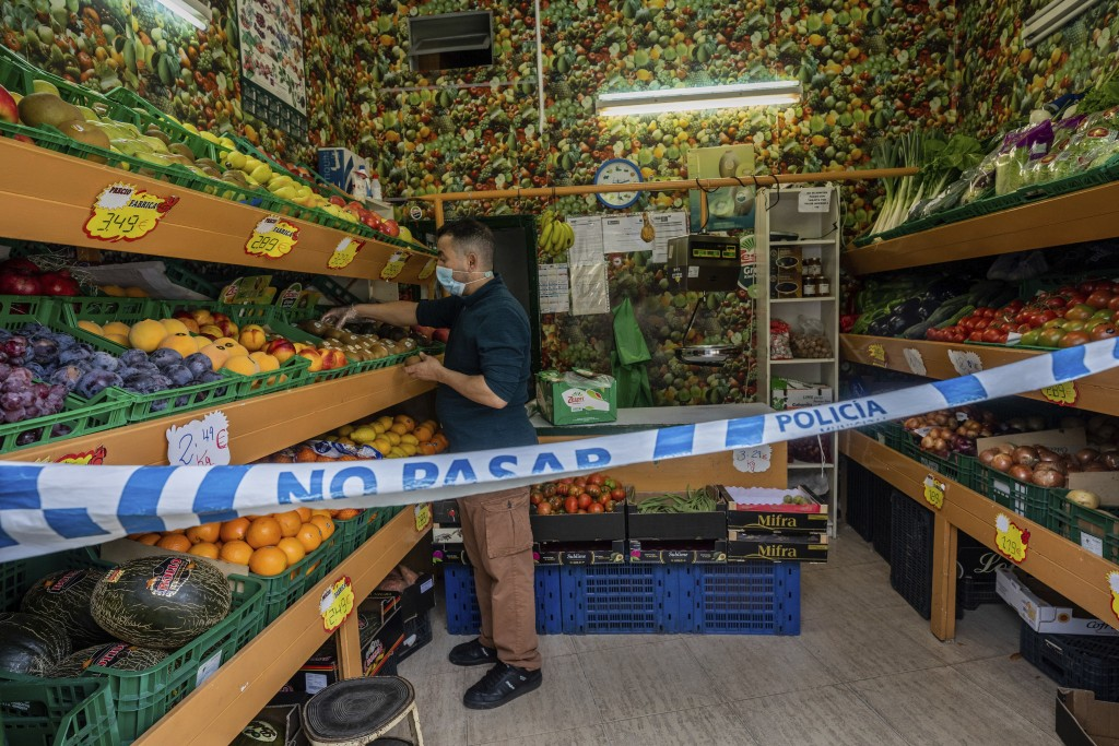 A no trespassing sign is used to keep social distance guidelines at a vegetable shop in Madrid, Spain, Tuesday, Oct. 6, 2020. Although the speed of ne...