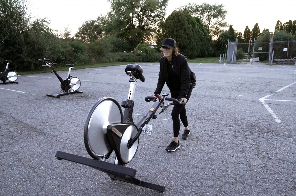 Jeanne Carter, co-owner of Fuel Training Studio, in Newburyport, Mass., removes stationary exercise bikes from a parking lot outside the gym following...