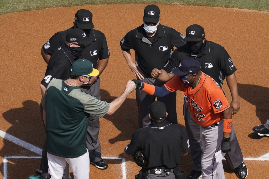 Oakland Athletics manager Bob Melvin, left, greets Houston Astros manager Dusty Baker Jr. as they meet with the umpire crew before Game 1 of a basebal...