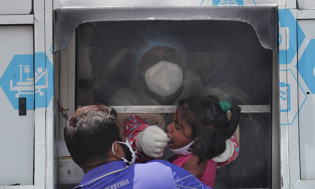 A Sri Lankan health official takes a swab sample from a girl to test for COVID-19 outside a hospital in Minuwangoda, Sri Lanka, Tuesday, Oct. 6, 2020....