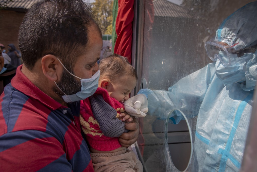 A Kashmiri health worker takes a nasal swab sample of a child to test for COVID-19 in Srinagar, Indian-controlled Kashmir, Tuesday, Oct. 6, 2020. Indi...