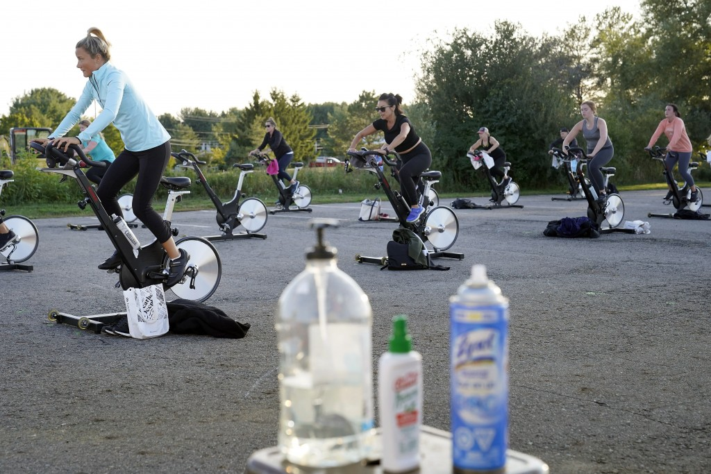 Jackie Brennan, of Merrimac, Mass., front left, pedals with others on stationary exercise bikes during a spinning class in a parking lot outside Fuel ...