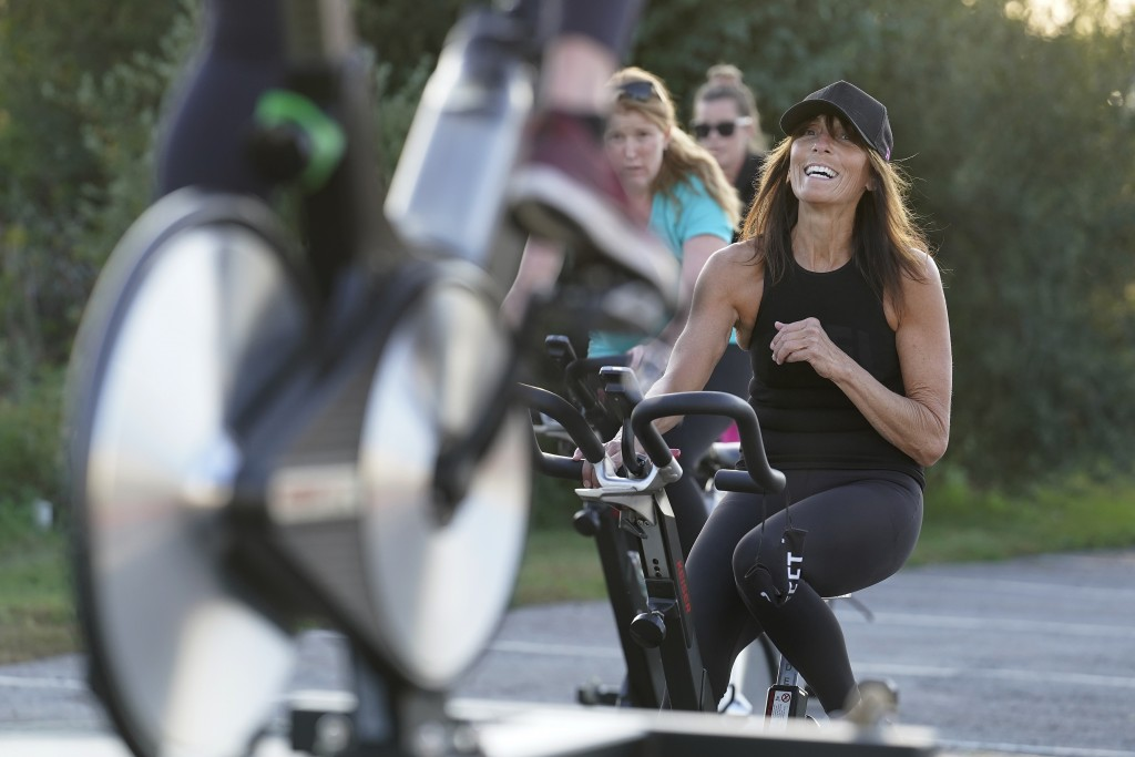 Jeanne Carter, co-owner of Fuel Training Studio, in Newburyport, Mass., right, works out on a stationary exercise bike during a spinning class in a pa...