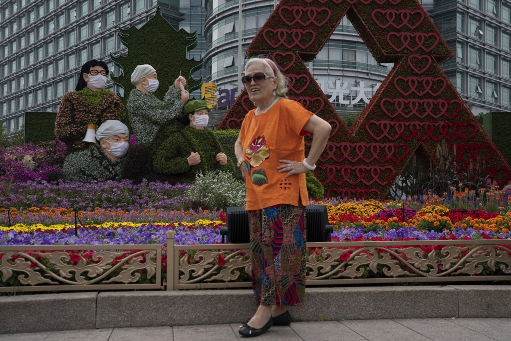 A woman poses for photos near floral decorations, honoring China's frontline workers who fought the COVID-19 outbreak, setup for the National Day holi...