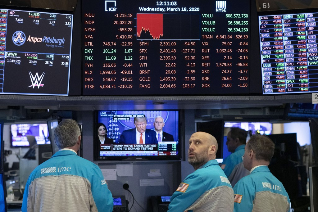 FILE - In this Wednesday, March 18, 2020 file photo, traders at the New York Stock Exchange watch President Donald Trump's televised White House news ...