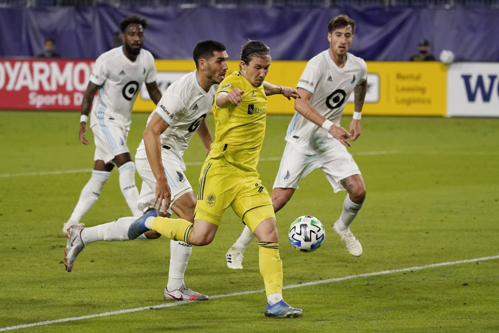 Nashville midfielder Alex Muyl, foreground, shoots in front of Minnesota United defenders during the first half of an MLS soccer match Tuesday, Oct. 6...