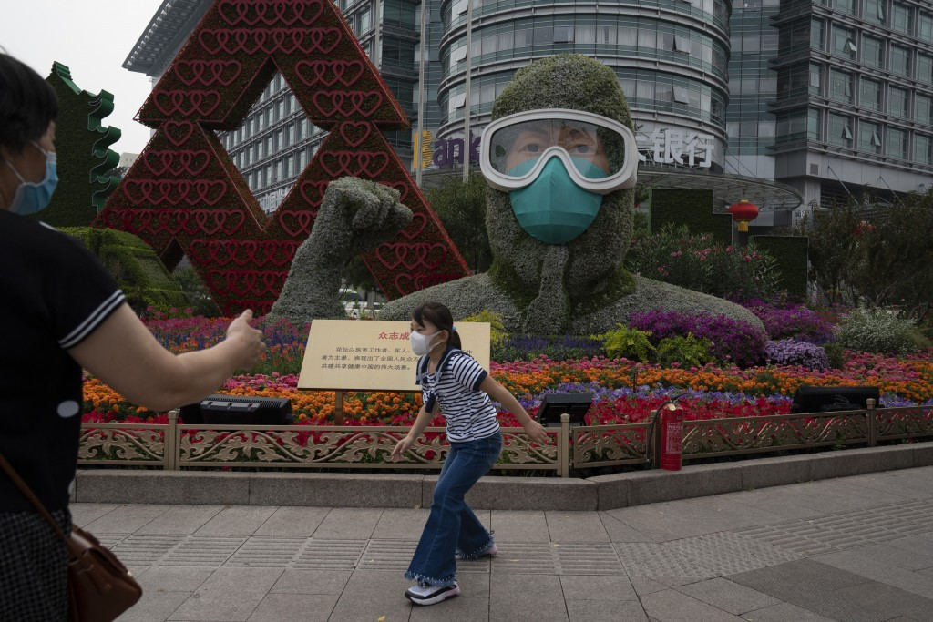 A Chinese girl wearing a mask to protect from the coronavirus runs past a floral decoration, honoring China's frontline workers who fought the COVID-1...