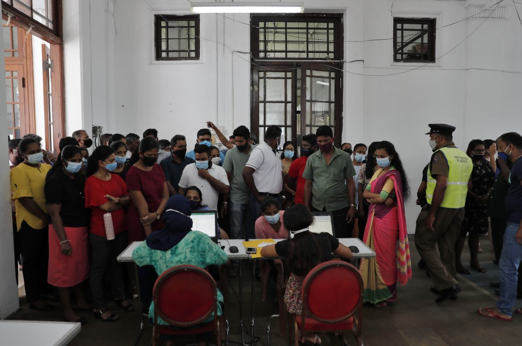 Employees of Colombo municipal council crowd around a table to give their swab samples to test for COVID-19 in Colombo, Sri Lanka, Wednesday, Oct. 7, ...
