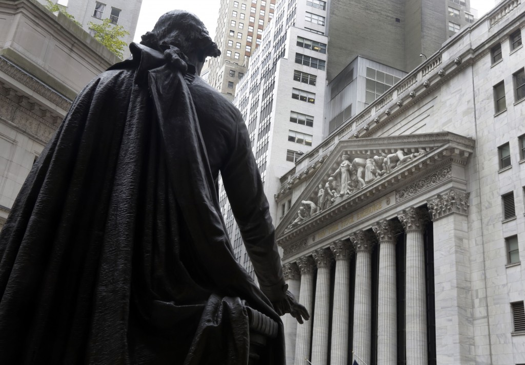 FILE - In this Oct. 2, 2014, file photo, a statue of President George Washington on the steps of Federal Hall faces the facade of the New York Stock E...
