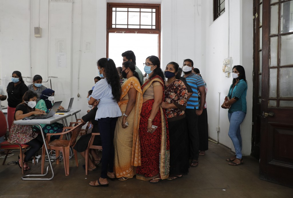 Employees of Colombo municipal council wait to give their swab samples to test for COVID-19 in Colombo, Sri Lanka, Wednesday, Oct. 7, 2020. Authoritie...