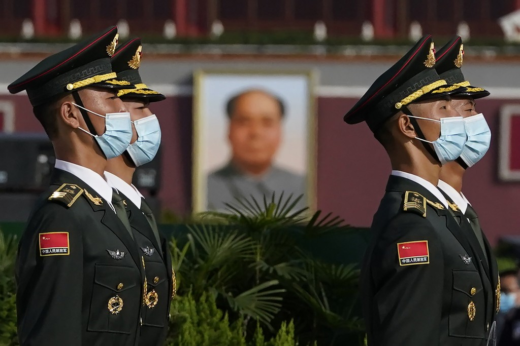 Chinese honor guards wearing masks to protect agains the coronavirus are seen near the portrait of late leader Mao Zedong during a ceremony held at th...