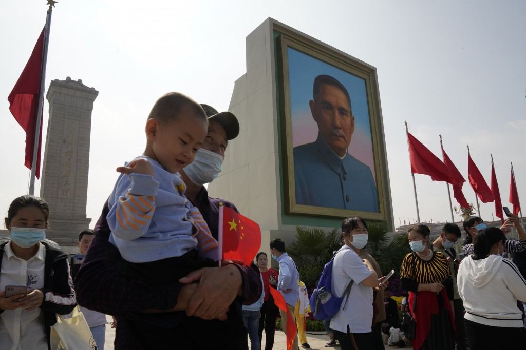 Tourists wearing masks to protect from the coronavirus stand near a portrait of Sun Yat-sen, who is widely regarded as the founding father of modern C...
