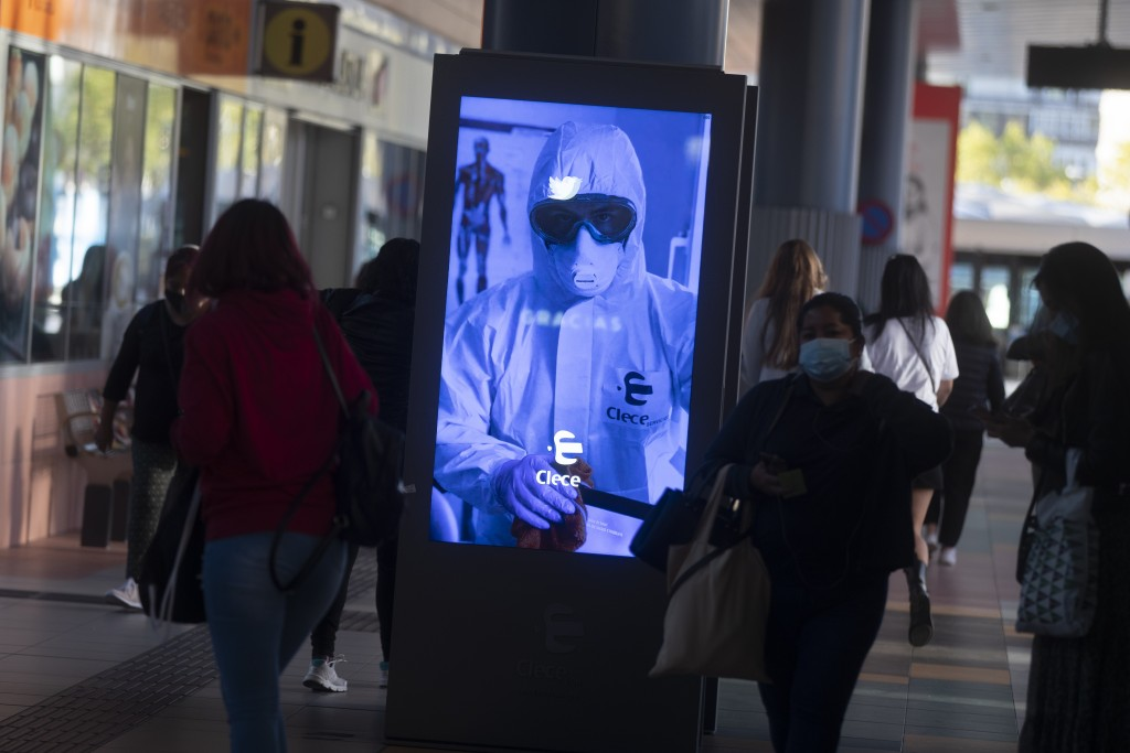 People pass by a poster thanking medical workers at a bus station in Madrid, Spain, Wednesday, Oct. 7, 2020. About 5.2 million people in Spain, includ...