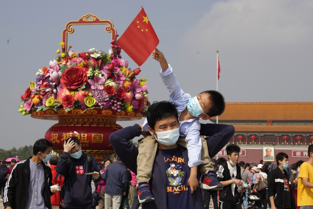 Tourists wearing masks to protect from the coronavirus stand near a floral decoration set up for the National Day celebrations on Tiananmen Square in ...