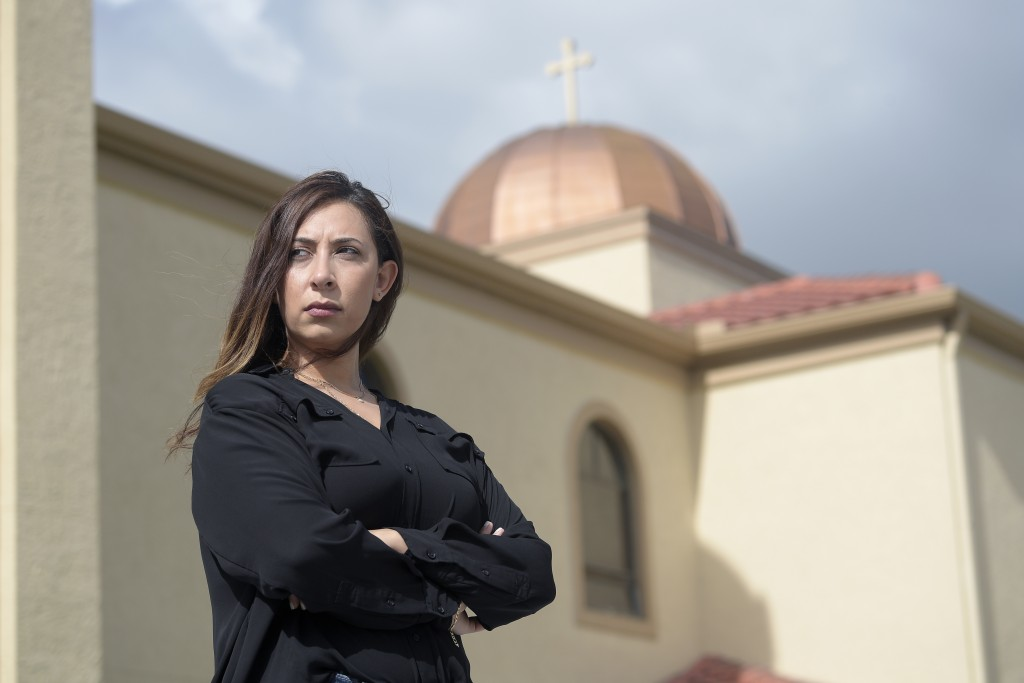 Sally Zakhari stands in front of the St. Mary & Archangel Michael Coptic Orthodox Church, Monday, Aug. 24, 2020, in Oviedo, Fla. Zakhari has alleged, ...