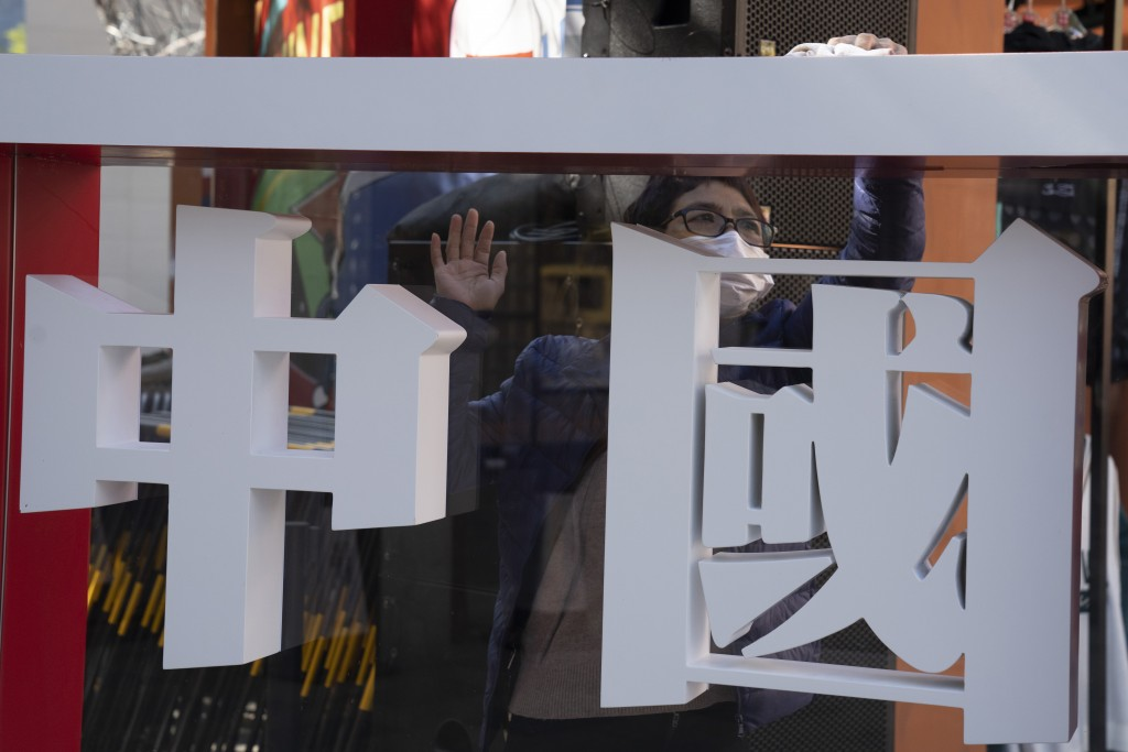 """A worker cleans the panel with the words """"China"""" written on it during a Chinese sporting goods brand promotion event in Beijing on Sunday, Oct. 4, 202..."""