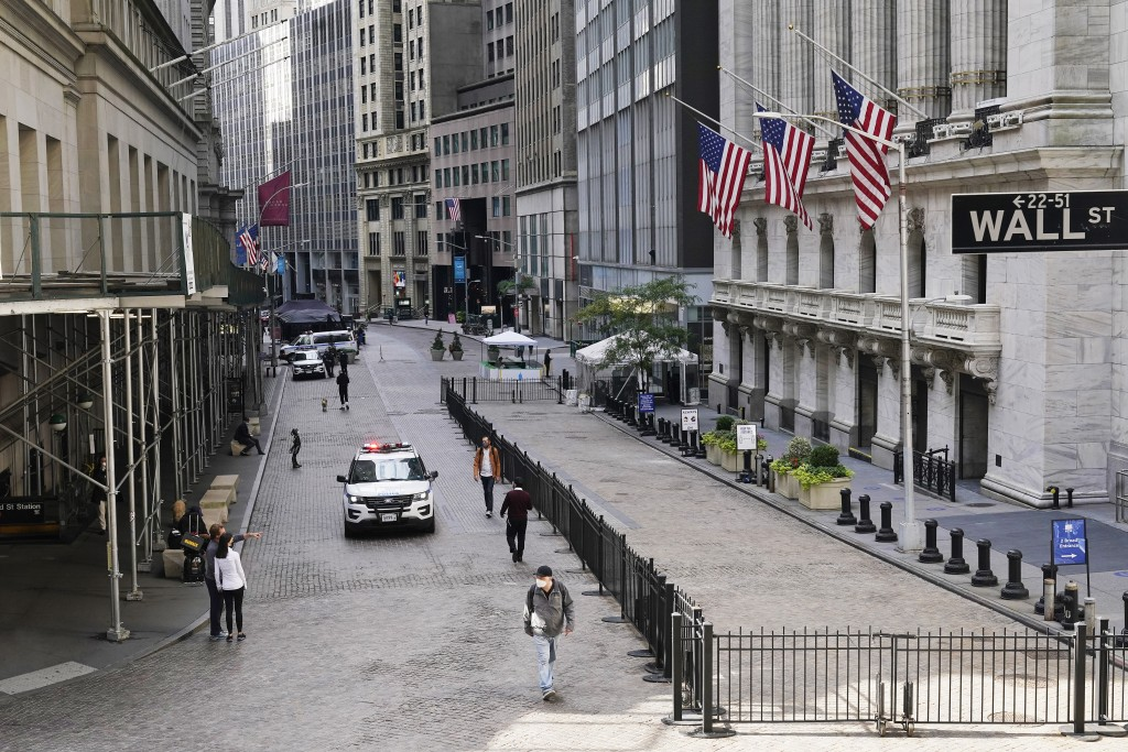 A police car patrols in front of the New York Stock Exchange, Wednesday, Oct. 7, 2020.  Companies retreated from deal-making as the virus pandemic stu...