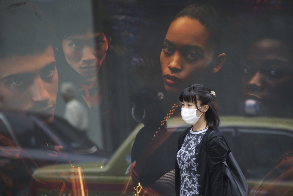 A woman wearing a face mask to protect against the spread of the new coronavirus walk at Ginza shopping district in Tokyo, Wednesday, Oct. 7, 2020. (A...