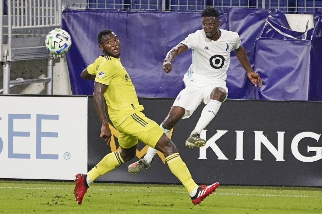 Minnesota United defender Bakaye Dibassy, right, passes the ball past Nashville midfielder Brian Anunga during the second half of an MLS soccer match ...