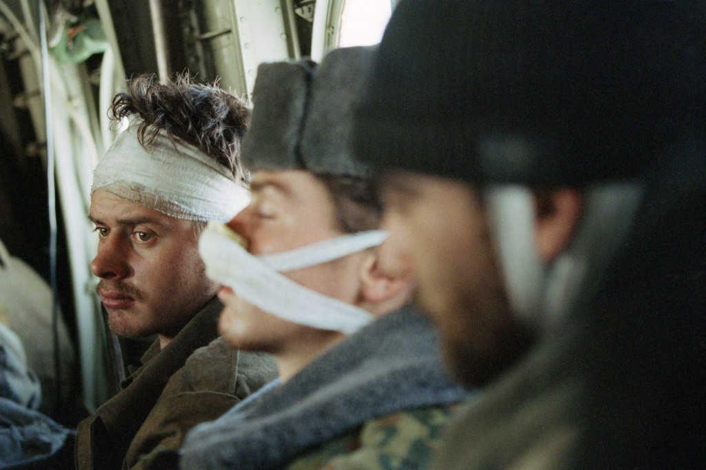 FILE - In this Feb. 3, 1995 file photo, a wounded Russian soldier, being evacuated with his comrades, look on, in a helicopter on his way out of Grozn...