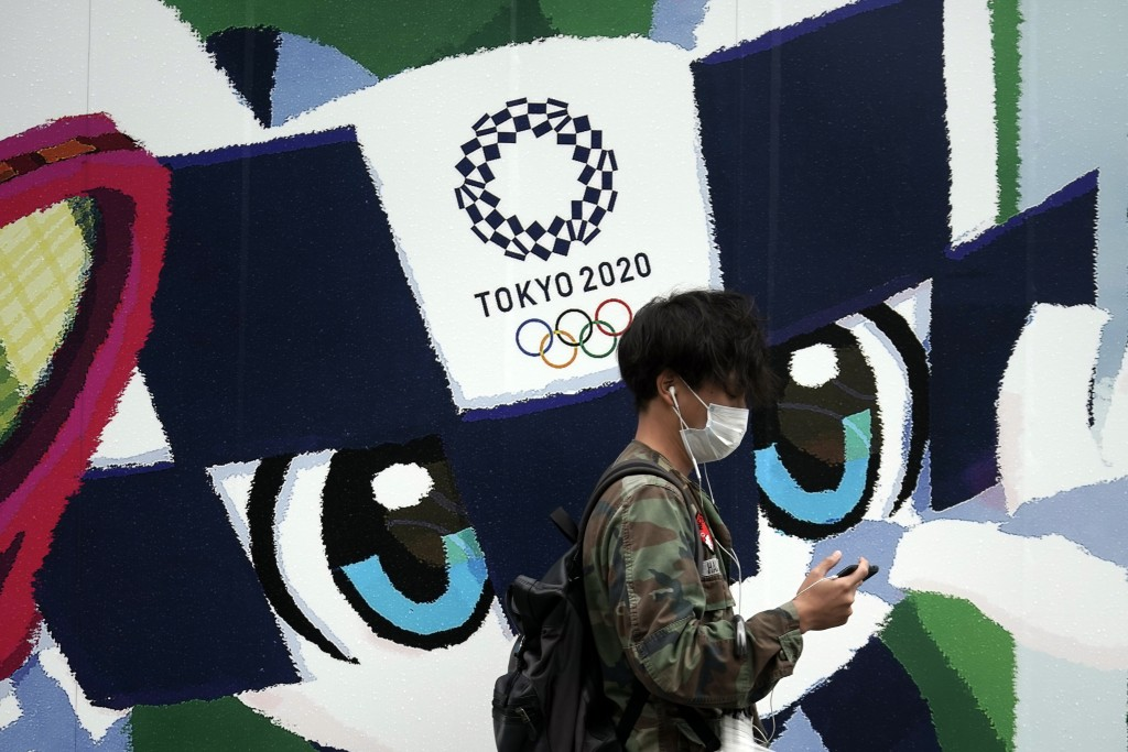 A man walks in front of an advertisement for the Tokyo 2020 Olympics Thursday, Oct. 8, 2020, in Tokyo. Typhoon Chan-hom is approaching Japan's main is...