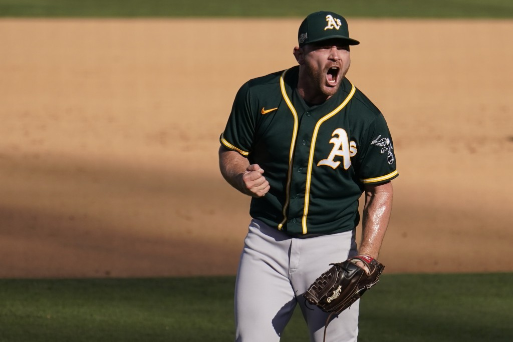 Oakland Athletics pitcher Liam Hendriks reacts after the Athletics defeated the Houston Astros in Game 3 of a baseball American League Division Series...