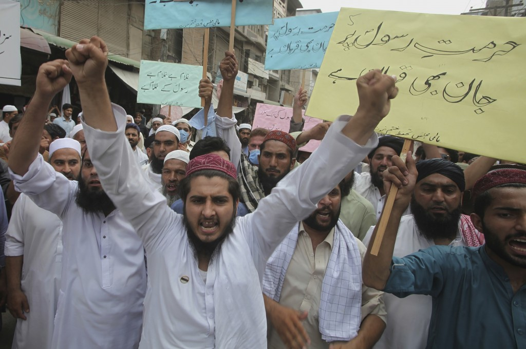 """FILE - In this July 31, 2020 file photo, supporters of a religious group chant slogans with placards that read, """"we can die for honor of Prophet"""" at a..."""