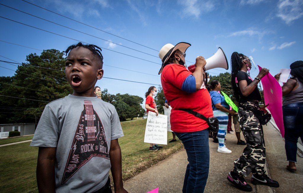 Protesters rally across the street from a lodging complex they claim is illegally evicting residents while failing to maintain the property on Wednesd...