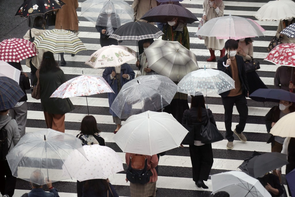 People walk across a pedestrian crossing in the rain Thursday, Oct. 8, 2020, in Tokyo. Typhoon Chan-hom is approaching Japan's main island with author...