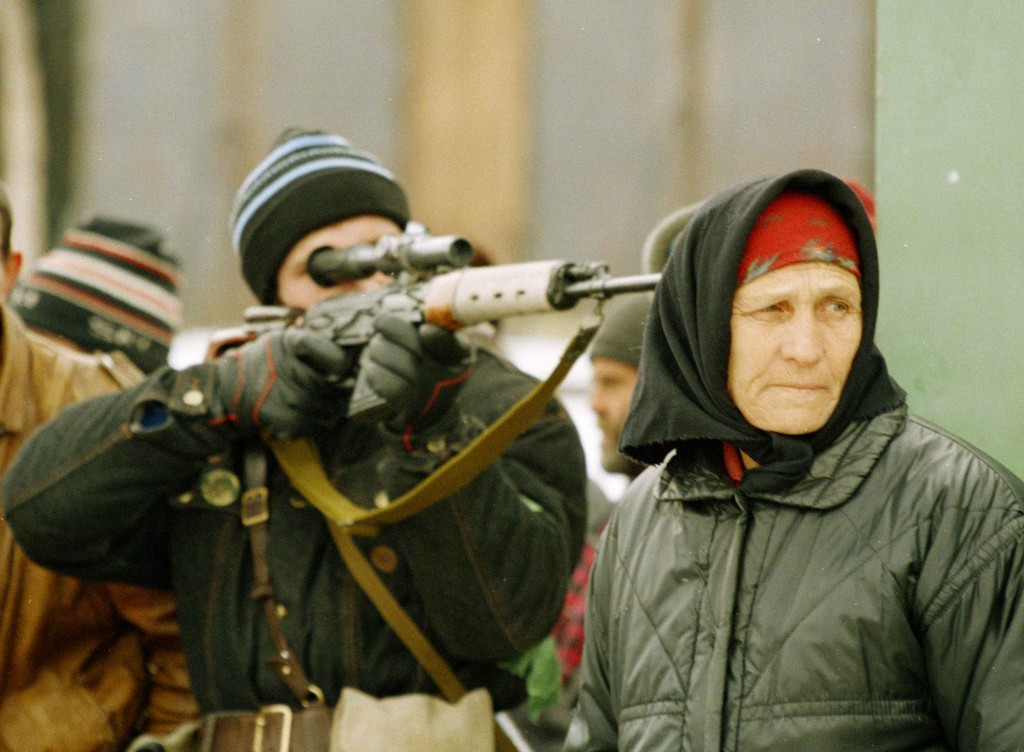FILE- In this  Jan. 25, 1995 file photo, a Chechen sniper takes aim as a woman looks on after a Russian sniper took a pot shot at a street market on t...