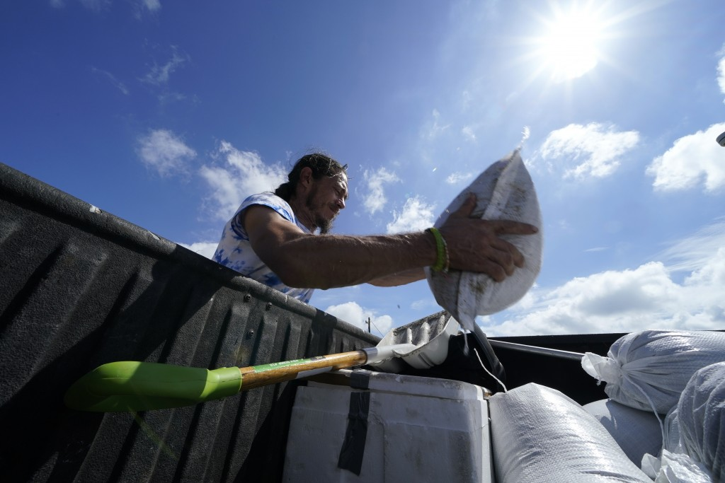 fill sandbags to protect their home in anticipation of Hurricane Delta, expected to arrive along the Gulf Coast later this week, in Houma, La., Wednes...