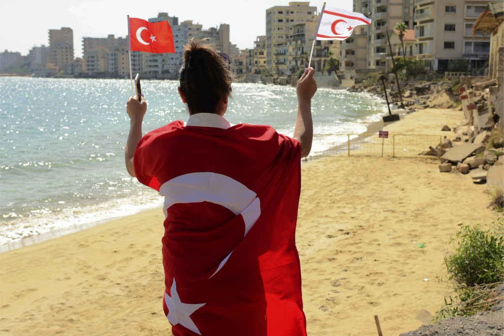 CORRECTS SPELLING OF LOCATION   A woman with Turkish and Turkish Cypriot breakaway flags walks along at the beach with abandoned hotels after police o...
