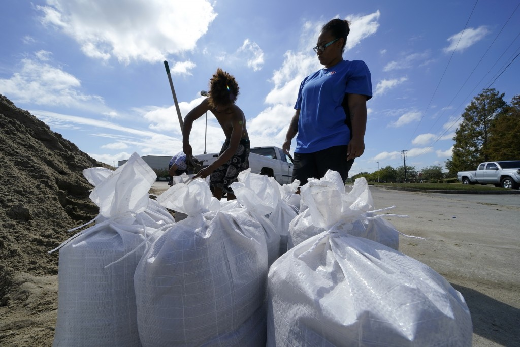 Stephanie Verrett and Jodie Jones fill sandbags to protect their home in anticipation of Hurricane Delta, expected to arrive along the Gulf Coast late...