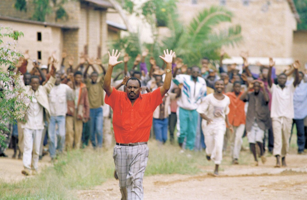 FILE - In this Wednesday, April 13, 1994 file photo, Rwandan refugees hold their hands up and ask for help from Belgian soldiers, who had come to a ps...