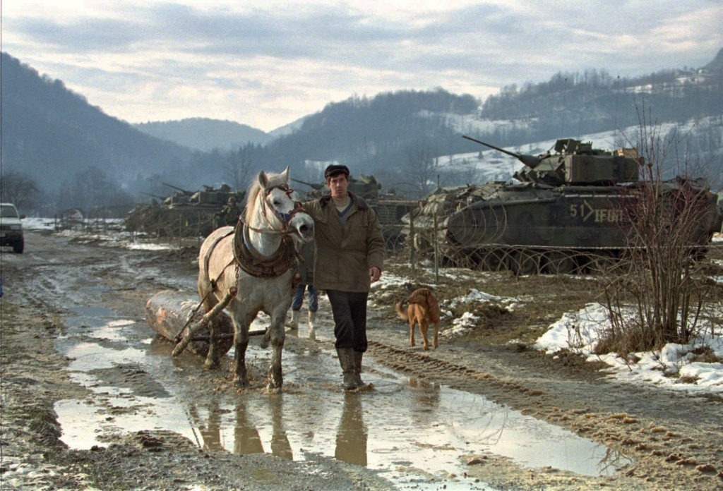 FILE - In this Sunday, Jan 7 1996 file photo, a Bosnian farmer guides his horses passing the base of the U.S. Alpha advance team of the 3/4 Cav. in St...