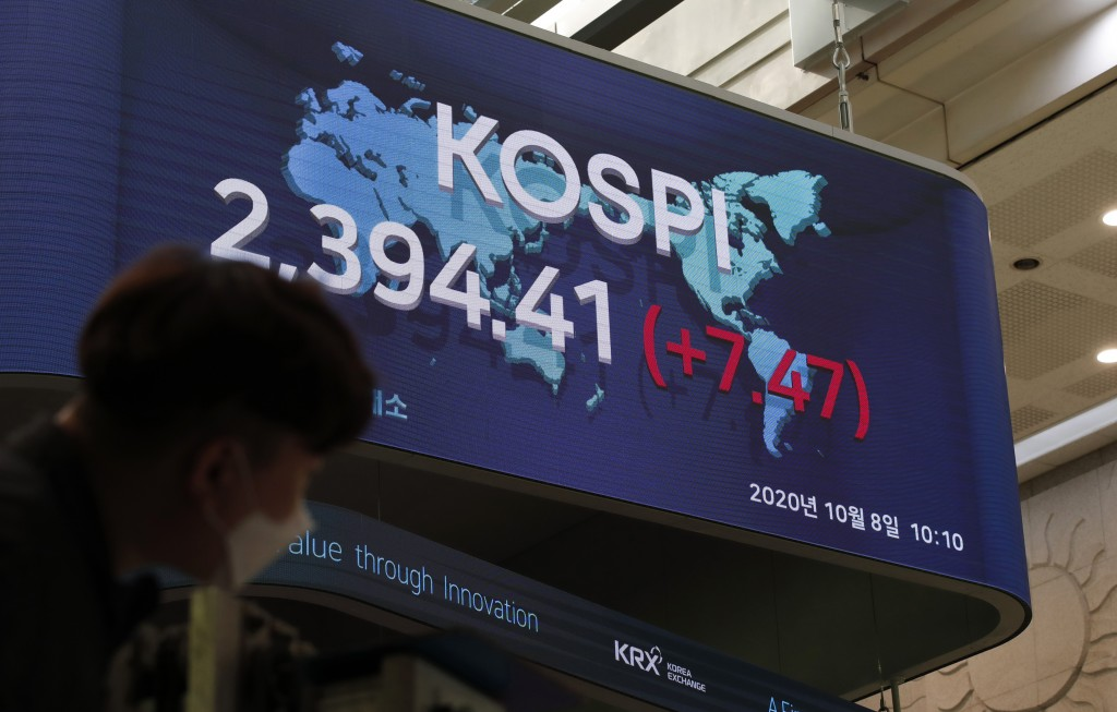 A man wearing a face mask stands near a screen showing the Korea Composite Stock Price Index (KOSPI) at the Korea Exchange in Seoul, South Korea, Thur...