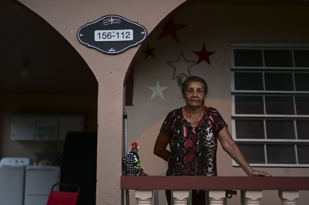 Candida Diaz poses for a photo by her homes' address number, which was registered for the first time by the iCasaPR, a nonprofit group that aims to st...