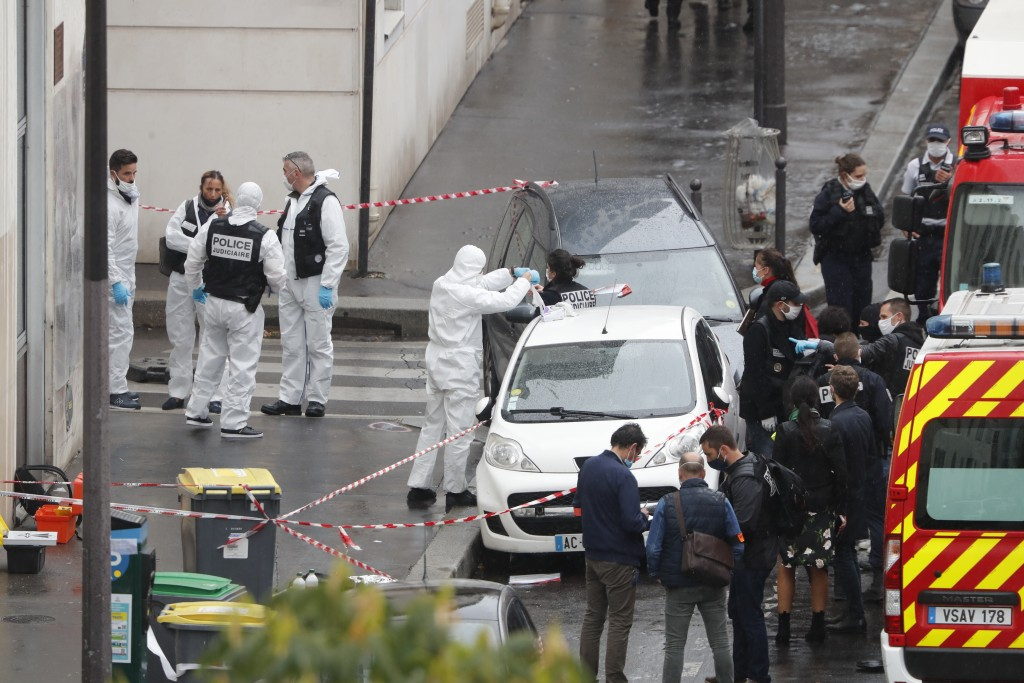 FILE - In this Sept. 25, 2020 file photo, police and forensic investigate an attack that wounded two people near the former offices of the satirical n...